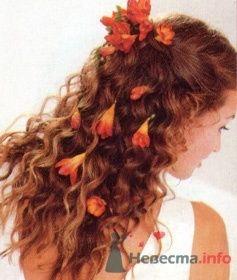 Прическа невесты распущенные локоны с оранжевыми цветами в волосах.