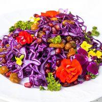 Салат из краснокочанной капусты, граната и изюма, оформленный цветками фиалки