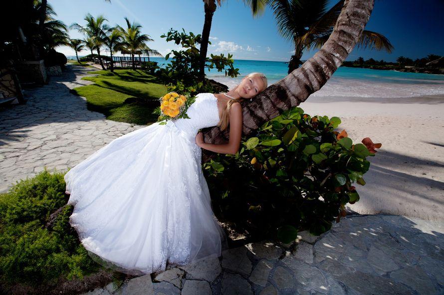 Невеста в белом пышном платье с желтым букетом в руке, прилегла на изогнутый ствол тропической пальмы, сзади виднеется море - фото 575708 GoldMLB - свадьба в Доминикане