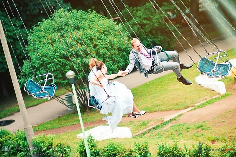 Жених и невеста, взявшись за руки, катаются на качелях