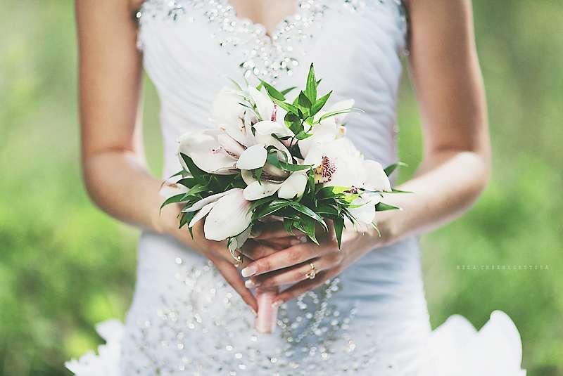невеста в белом платье, обильно расшитом стразами, с букетом невесты из зелени и белых орхидей в руках  - фото 1392197 Фотограф Людмила Черноскутова