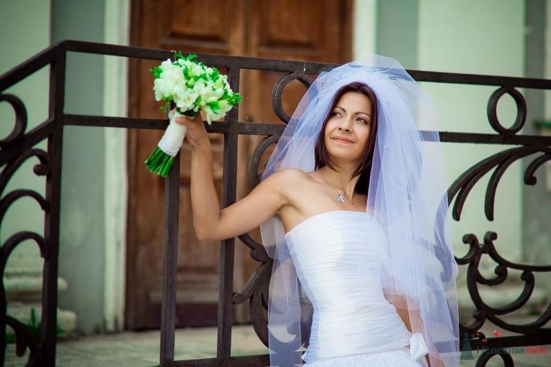 Невеста с букетом белых цветов стоит на фоне деревянной двери