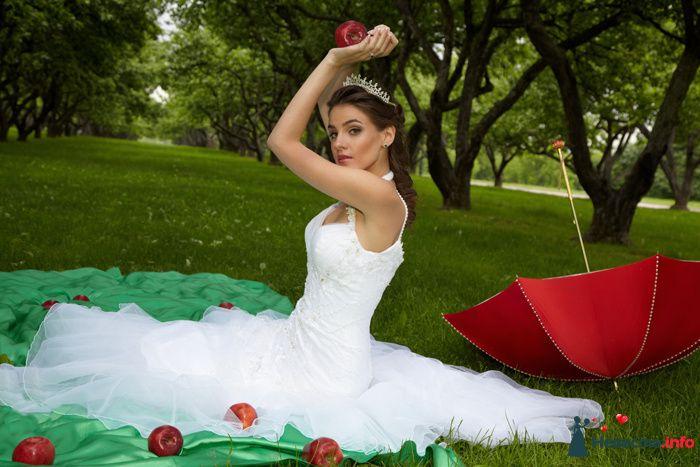 Невеста с яблоком в руках сидит на траве возле красного зонта