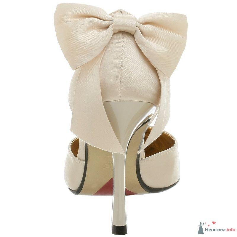 Белые туфли на высокой шпильке, над каблуком большой бантик.