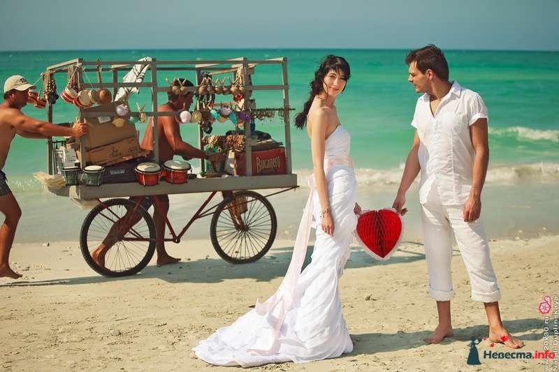 На песчаном побережье стоят молодожены в белоснежных одеждах, в руках у них импровизированное алое сердце, позади пляжный - фото 113800 Фотограф Наталья Дуплинская