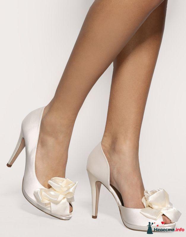 Белые туфли на высоком каблуке, с открытым носком спереди бантик.