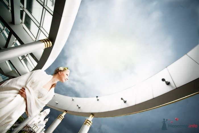 Невеста в белом длинном платье стоит на фоне здания