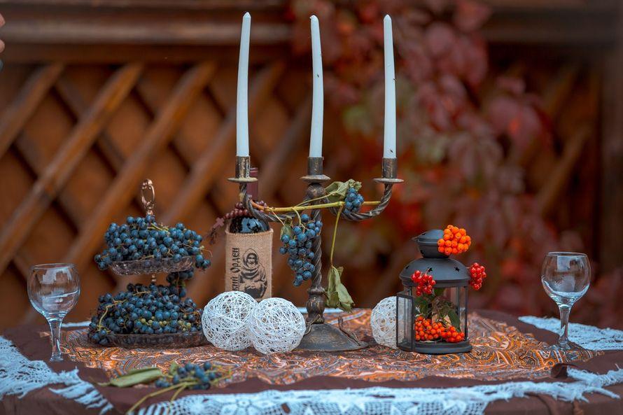 Подсвечник, украшенный виноградом, белые декоративные шары, коричневый подсвечник-фонарик, украшенный рябиной, на столе с - фото 2026534 Свадебное агентство All Inclusive