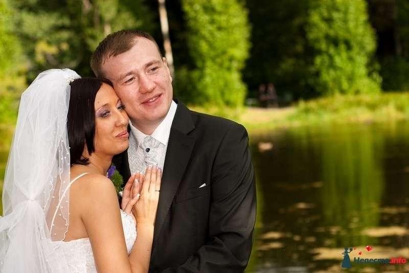 Жених и невеста, прислонившись друг к другу, сидят на фоне зелени и пруда - фото 87364 Amatour