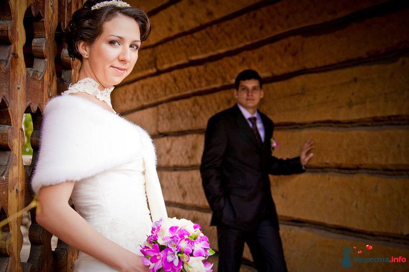 Жених и невеста стоят возде деревянной стены