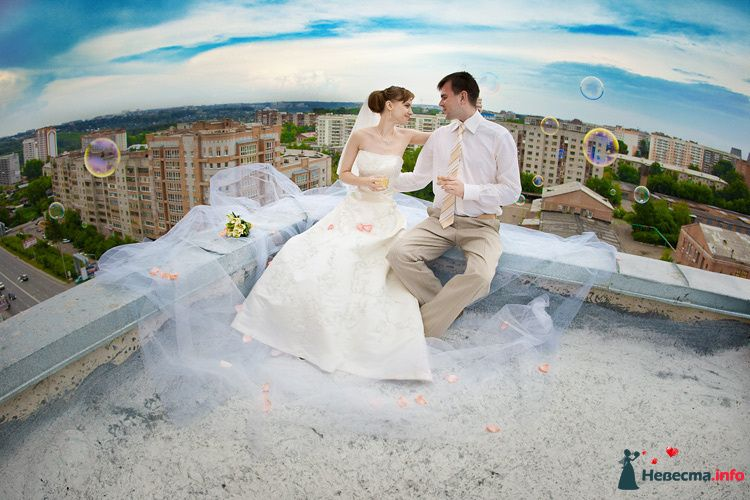 Жених и невеста сидят, прислонившись друг к другу, на крыше дома - фото 90841 LevBodrov