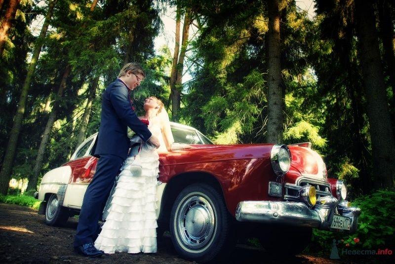 """Красная """"Победа"""" на фоне зелени парка и счастливой пары."""