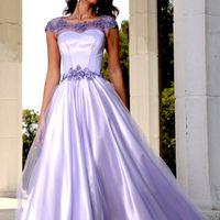 Среди белых колонн стоит подружка невесты в длинном двухслойном сиреневом платье  с расклешенным низом, декорированным сиреневым кружевом по верху приталенного лифа и на талии