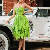 Подружка невесты в зеленом платье миди с корсажем, декором по центру лифа, многоярусной юбкой, в бежевых туфлях на шпильке положила руку на ретромобиль