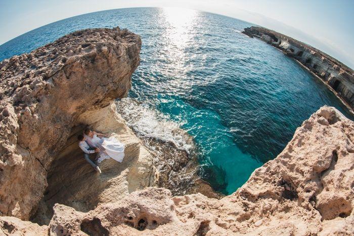 На пляже, в лагуне, сидят под сводом скалы, жених и невеста, она в белом платье, он в белой рубашке и серых брюках - фото 1579425 Агентство Гименей - организация свадеб на Кипре