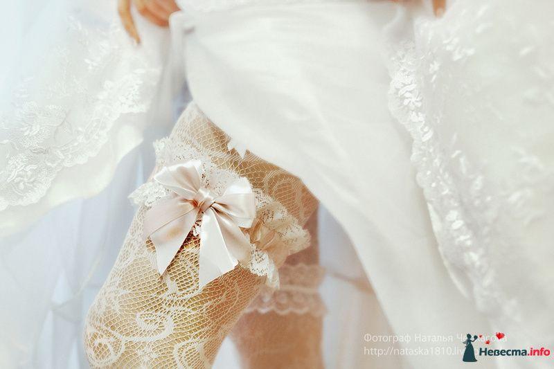 На ноге невесты белые колготки с с рисунком и кружевная подвязка  с