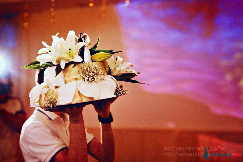 Парень несет на руках поднос на котором свадебный торт, украшенный