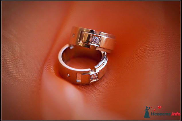 Золотые обручальные кольца с драгоценными камнями на фоне оранжевой ткани. - фото 81830 Невеста01