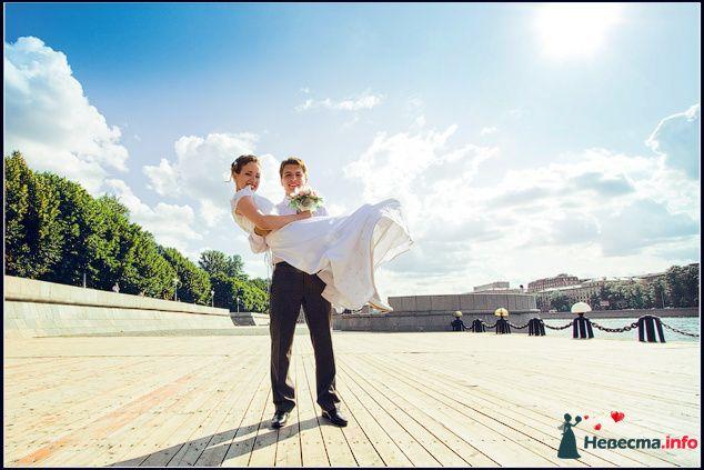Жених держит на руках невесту на фоне облачного неба