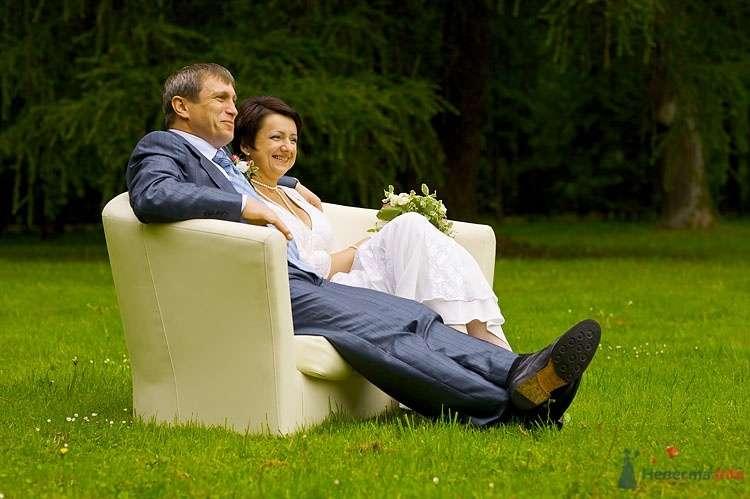 Жених и невеста, прислонившись друг к другу, сидят в кресле на улице на фоне зелени - фото 31207 Свадебная мастерская ОП-позиция
