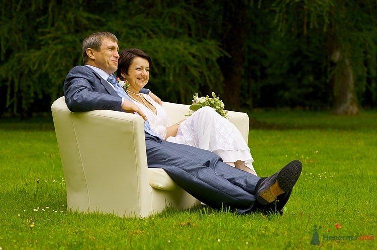 Жених и невеста, прислонившись друг к другу, сидят в кресле на улице