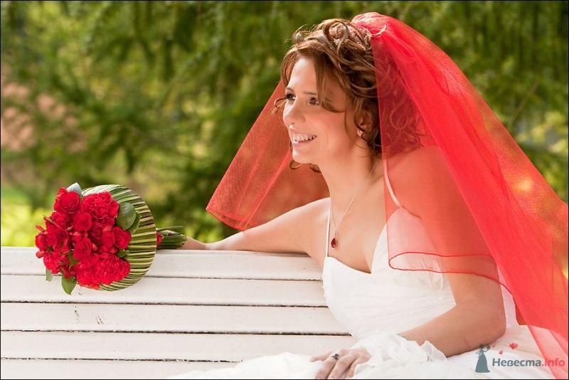 Невеста в красной фате сидит на белой скамейке