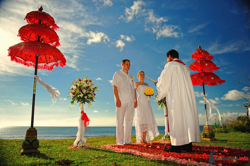 Молодая пара в белых нарядах  проводит церемонию выездного бракосочетания на острове в океане, стоя на кофре из красных цветов - фото 115330 Ваш фотограф на Бали - Максим Коробейников
