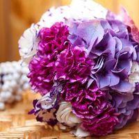 Букет невесты из малиновых гвоздик, сиреневых гортензий, сиренево-белых эустом, декорированный белыми бусами