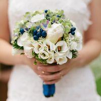 Невеста в белом платье с букетом из белых эустом и пионов, зеленых гортензий и синих ягод, декорированный синей лентой