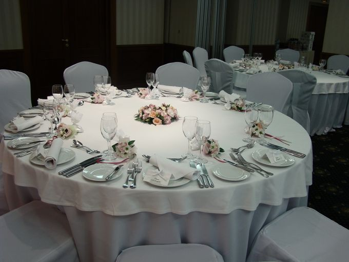 Украшение стола гостей: в центре стола композиция с кустовой розой и лизиантусами, для каждого гостя разложены минибукетики-комплименты