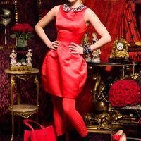 """В красной комнате подружка невесты в красном коротком атласном платье, приталенным лифом без рукава, декоративным воротничком с камнями, юбкой """"бочонок"""", в красных колготах и черных замшевых полусапожках."""