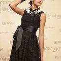 Подружка невесты в черном коротком кружевном платье с атласным поясом, с белым кружевом и черной рюшей на горловине отделенных атласной ленточкой, на руке черный кружевной манжет
