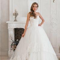 Пышное свадебное платье Кира с шикарным шлейфом. Юбка платья украшена высоким объемным кружевом и придает платью удивительный шарм и очарование роскоши. Корсет свадебного платья расшит бисером, жемчугом и хрусталем. Прекрасный выбор невесты, желающей не п