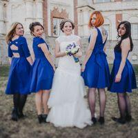 Возле замка невеста в длинном платье с гипюром, заниженной талией держит букет из белых, голубых цветов и подружки в синих платьях миди с V-образным вырезом на спине, рукавом три четверти и открытой спиной