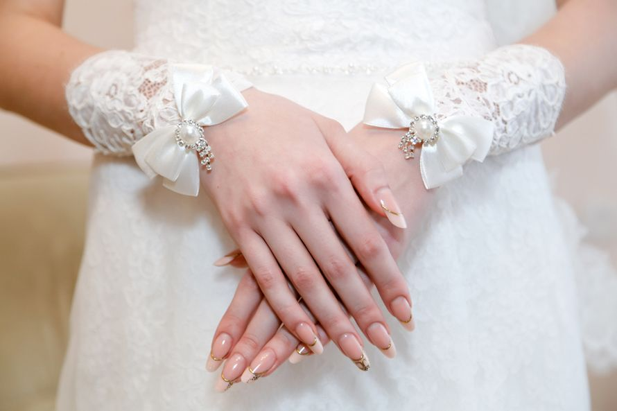 Руки невесты на фоне свадебного платья, маникюр - бежевый френч, украшенный золотом. - фото 1779447 Фотограф Ерошин Тарас