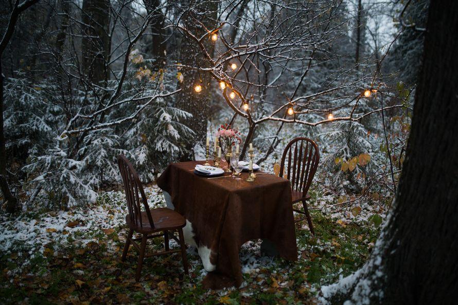 """Посреди зимнего леса, стоит коричневый стол с подсвечниками, тарелками и вазой цветов, рядом два коричневых стула, а сверху - фото 3197685 Свадебное агентство """"Wedkitchen"""""""
