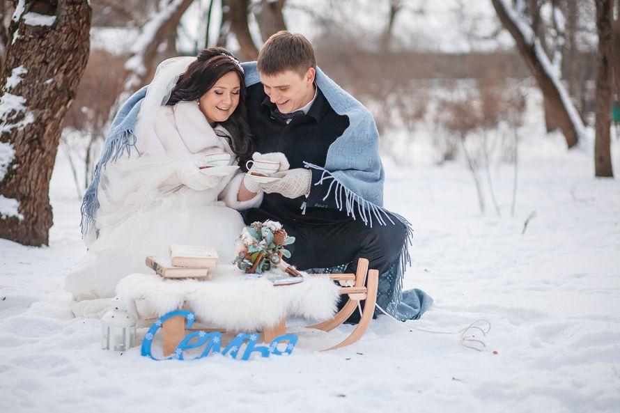 Жених и невеста сидят возле саней, укрывшись голубым пледом, на фоне зимних деревьев - фото 1953101 Alexandra_d