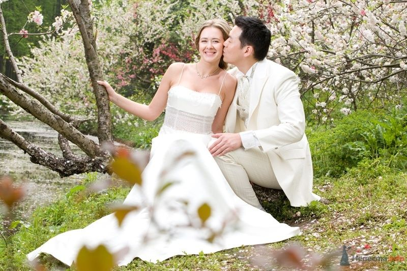 Жених и невеста сидят, прислонившись друг к другу, на фоне зелени - фото 35022 YuBinLi