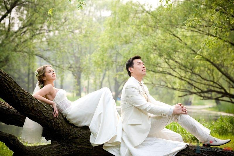 Жених и невеста стоят, прислонившись друг к другу, на фоне зелени и озера - фото 35023 YuBinLi