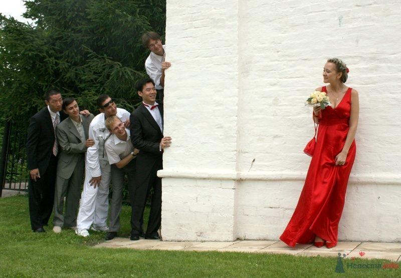 Невеста и жених с друзьями стоят друг на против друга возле белого здания - фото 35054 YuBinLi