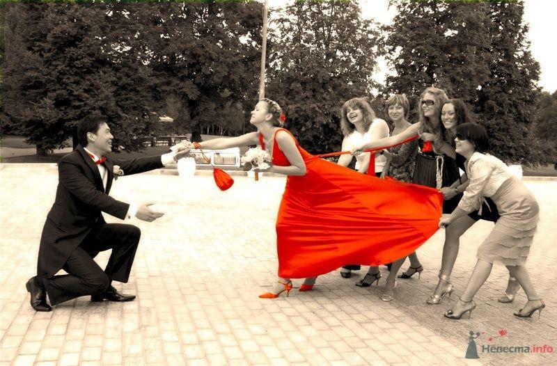 Жених и невеста, взявшись за руки, стоят на площади между гостями