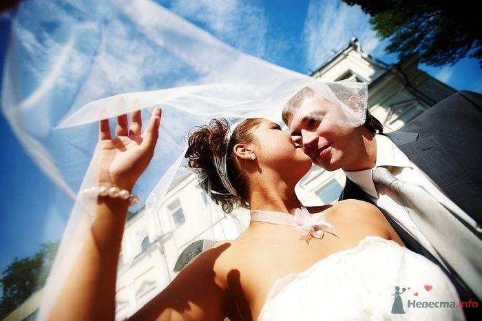 Жених и невеста, прислонившись друг к другу, стоят на фоне белого