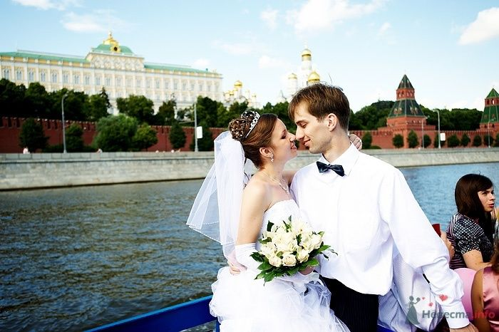 Жених и невеста стоят, прислонившись друг к другу, возле озера