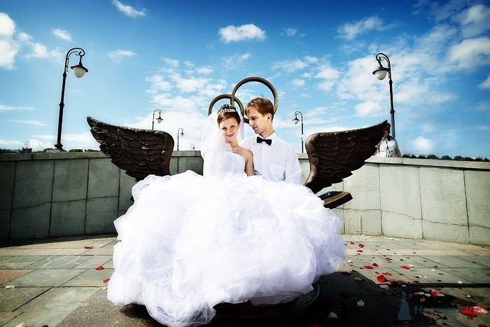 Жених и невеста сидят, прислонившись друг к другу, на скамейке