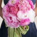 Розовый букет невесты из розовых гортензий, пионов и георгин, завязанный широкой зелено-белой лентой на бант