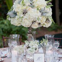 Оформление стола гостей композицией на высокой вазе в бело-серой гамме с гортензией, брунией и розами