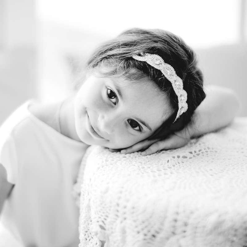Девочка в белом платье с коротким рукавом, на голове белый обруч с камнями, сидит у столика, украшенного кружевной скатертью - фото 3433501 Свадебный Фотограф Александр Поляков