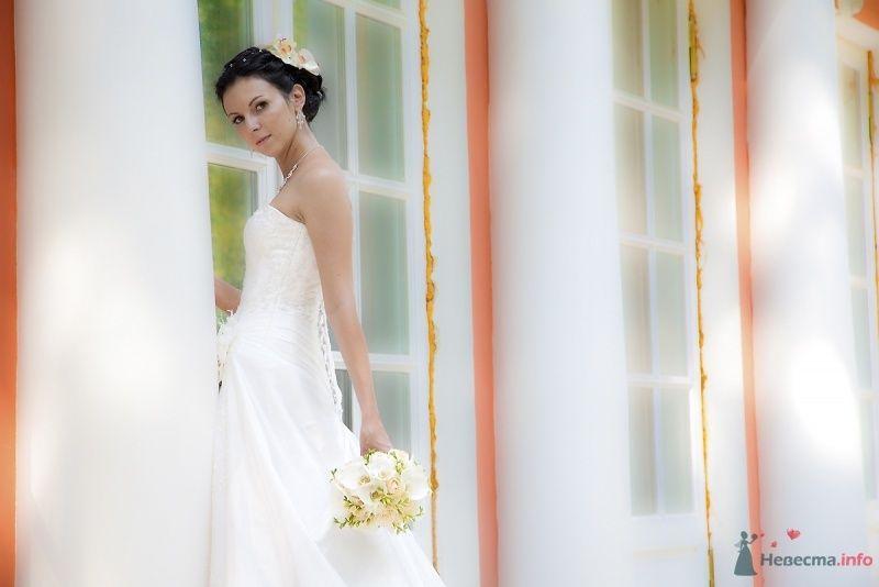 Невеста в белом длинном платье стоит у окна