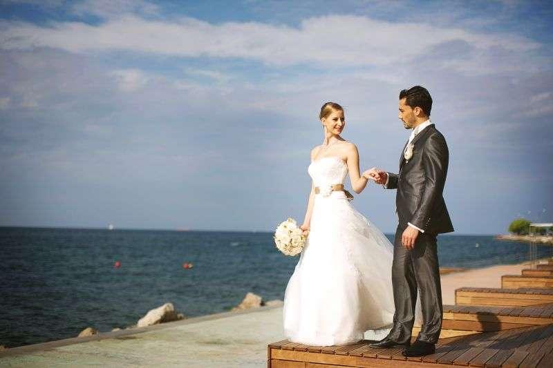 На деревянном причале стоит жених в блестящем черном костюме и держит за руку невесту в белоснежном пышном платье с букетом белых - фото 2610585 Агентство Интерус - свадьбы в Словении