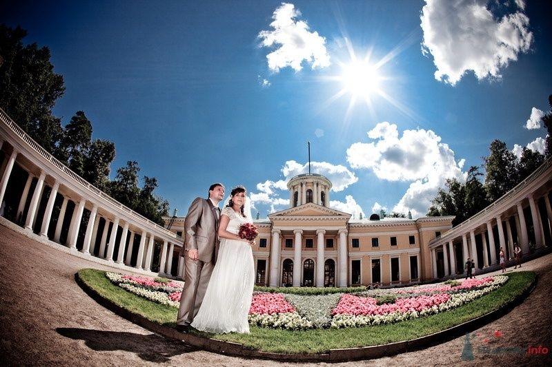 Жених и невеста стоят, прислонившись друг к другу, на фоне большого